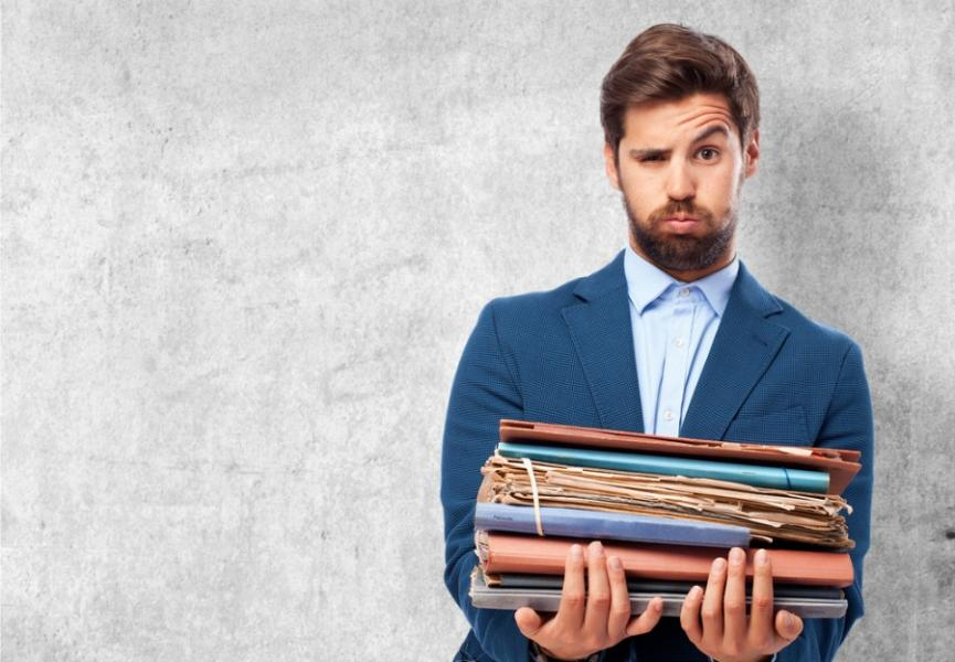 Bored Businessman in Office Holding Old Files