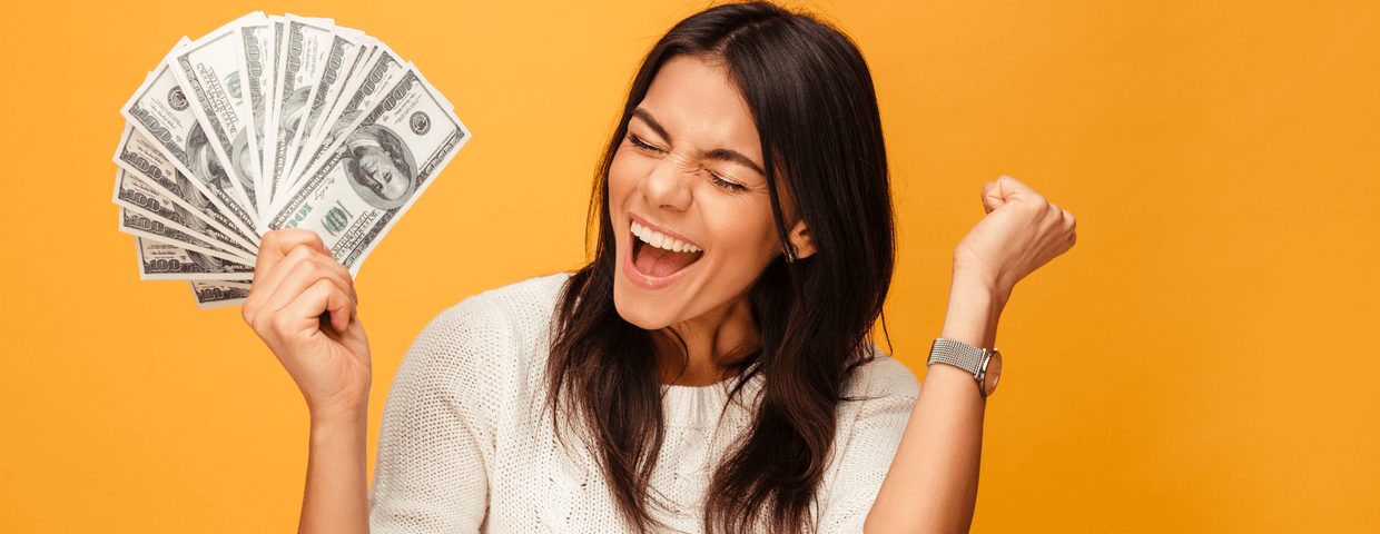 Portrait of a cheerful young woman holding money and celebrating in front of an orange background