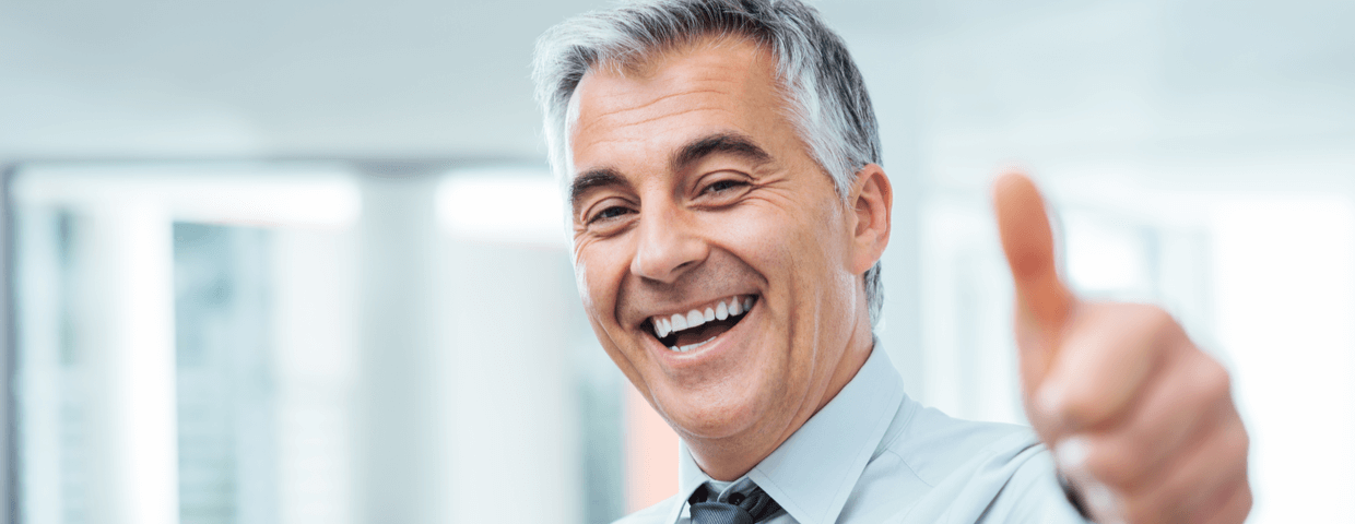 Business man smiling in office setting while holding thumb up.