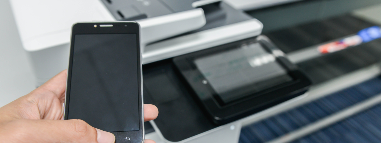 Person holding smart phone above printer