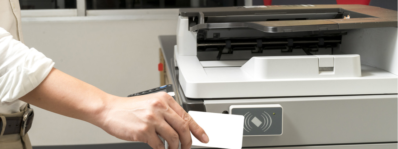 Person scanning badge on printer